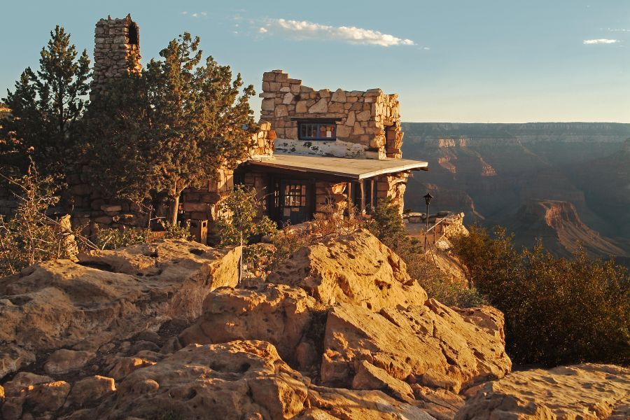A rustic lookout made of stone sits on the edge of the Grand Canyon.