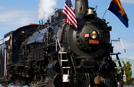 A black steam engine train with an American flag on the front.